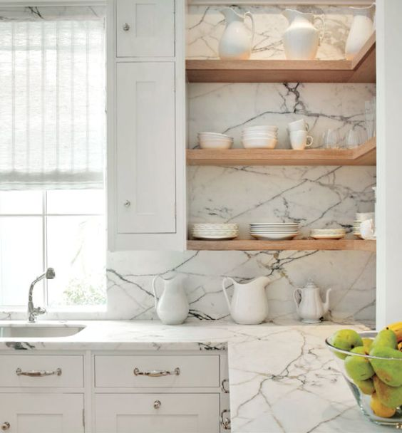 a white farmhouse kitchen with open shelving, built-in lights and a luxurious white marble backsplash and countertop