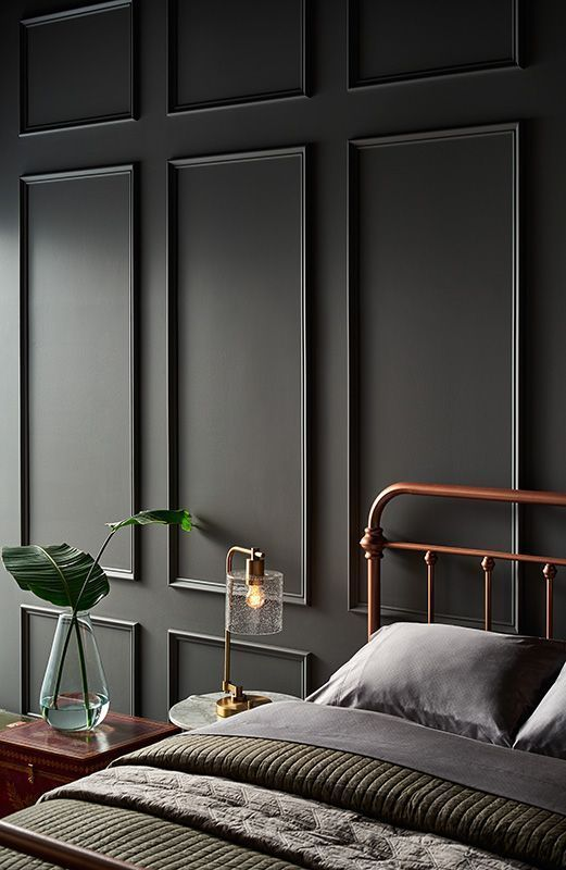 a chic vintage bedroom with a black paneled wall for an accent and some vintage furniture feels and looks very calm