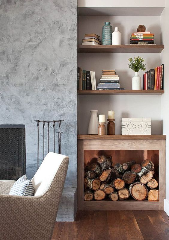 a small plywood open cabinet with firewood next to the fireplace doubles as a storage unit and a decoration