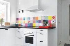 18 a white kitchen with black countertops and handles, with a super colorful tile backsplash looks very bold and accented