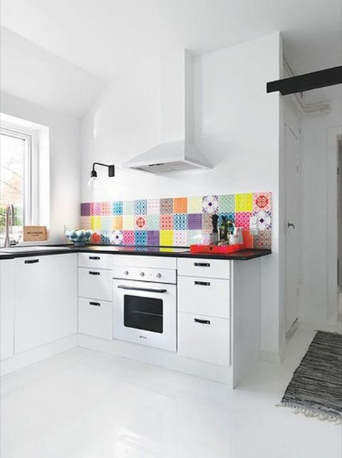 a white kitchen with black countertops and handles, with a super colorful tile backsplash looks very bold and accented