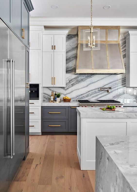 an art deco kitchen with grey and white cabinets, a metal hood, touches of gold and white marble countertops and a backsplash
