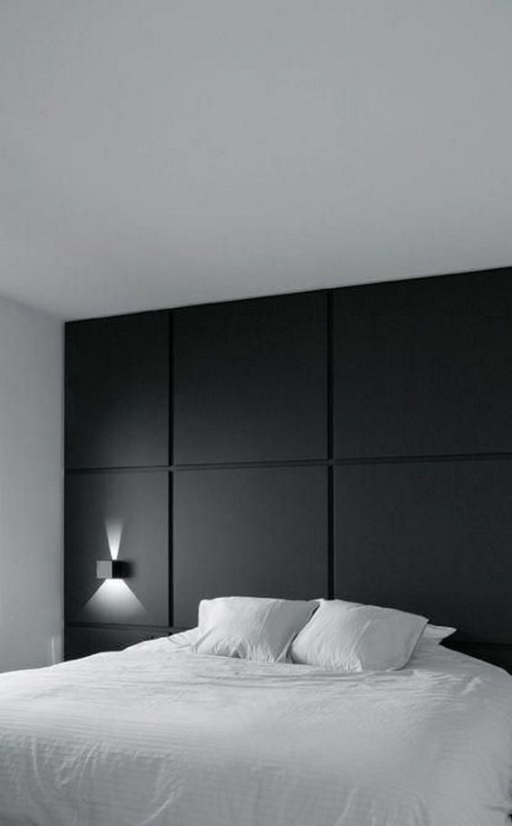 a minimalist bedroom with a black paneled wall for an accent and all neutrals around is a chic and cool space with a calm feel