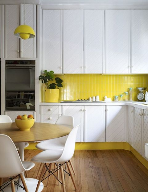 a white textural kitchen with a bright yellow tile backsplash and other touches of sunny yellow to echo with it