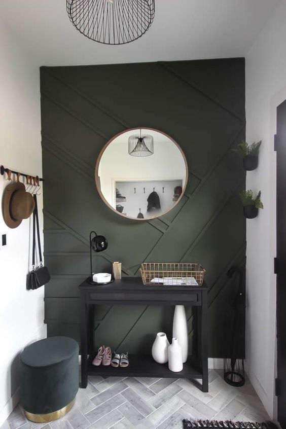 a modern entryway done in neutrals and with a black paneled wall plus some dark furniture for a very chic and cool look