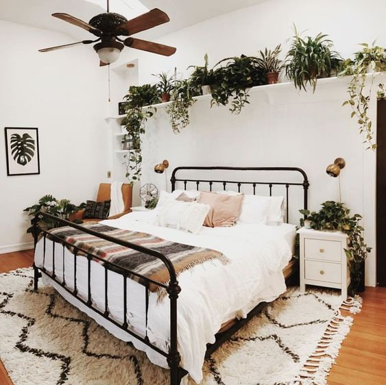 a whole shelf over the bed with potted greenery and plants all around and some greenery artworks