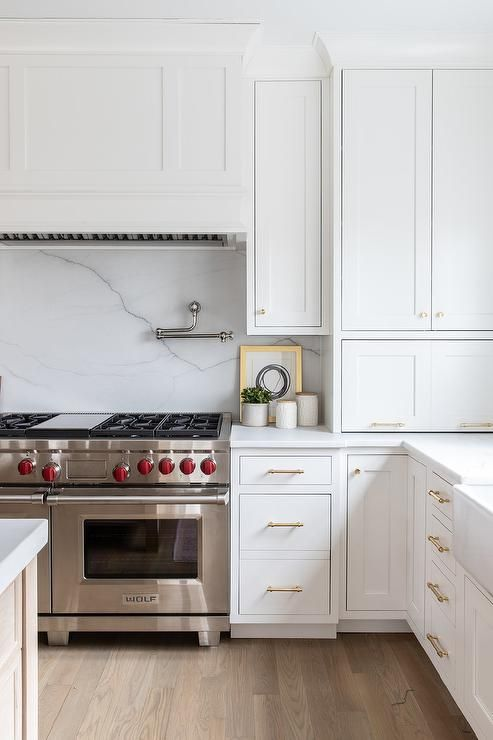 an elegant white kitchen with chic cabinets, gold touches and a white marble backsplash for a refined touch