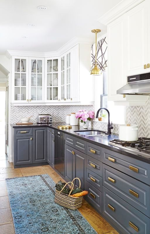 grey and white cabinets with a chevron tile backsplash and brass touches plus a blue rug