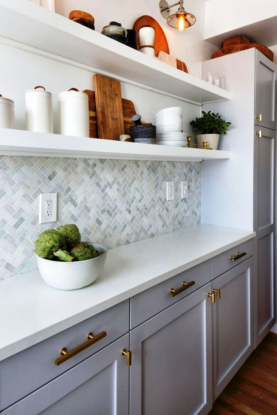 a catchy modern white kitchen with a marble tile backsplash, open shelving and touches of gold for more chic and elegance
