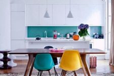 21 a minimalist white kitchen with a bright turquoise glass backsplash and bright chairs including a turquoise one to echo with it