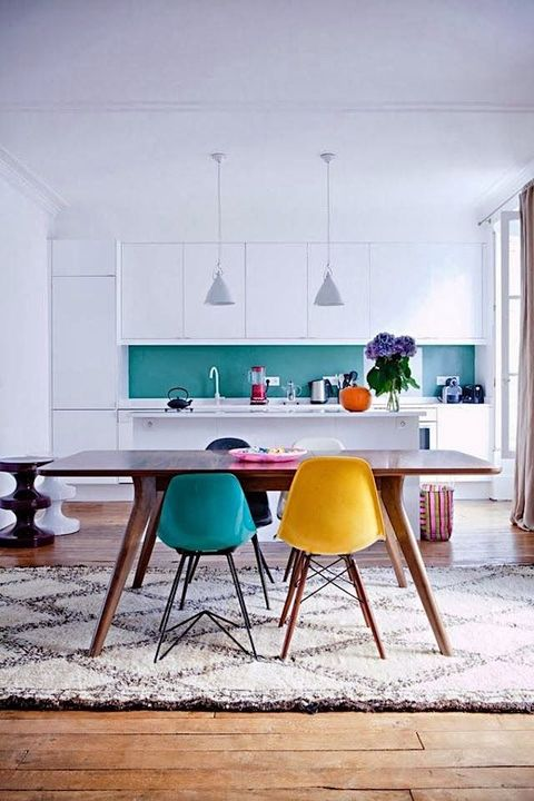 a minimalist white kitchen with a bright turquoise glass backsplash and bright chairs including a turquoise one to echo with it