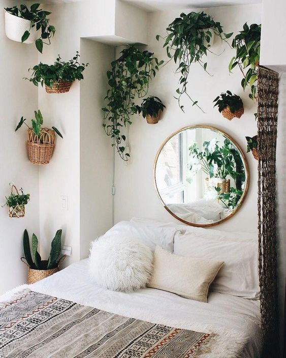 greenery in pots attached to the walls is ideal for this small boho bedroom