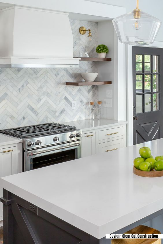 a farmhouse kitchen in graphite grey and white, with gold touches, wooden shelves and a catchy marble tile backsplash