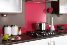 22 a minimalist white kitchen with dark wooden countertops and a bright pink glass backsplash for a bold touch