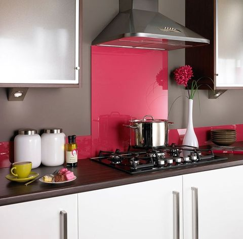 a minimalist white kitchen with dark wooden countertops and a bright pink glass backsplash for a bold touch