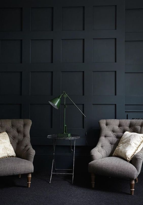a moody living room with a black panel accent wall that adds geometry, pattern and texture to the space