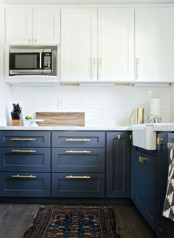 navy and white is always a timeless solution, a white subway tile backsplash is a cool idea and brass handles add chic