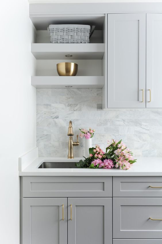 a grey farmhouse kitchen with a white countertop and a grey marble tile backsplash plus some touches of gold