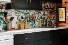 23 a monochromatic kitchen with a vintage touch and a bold botanical wallpaper backsplash is a unique idea