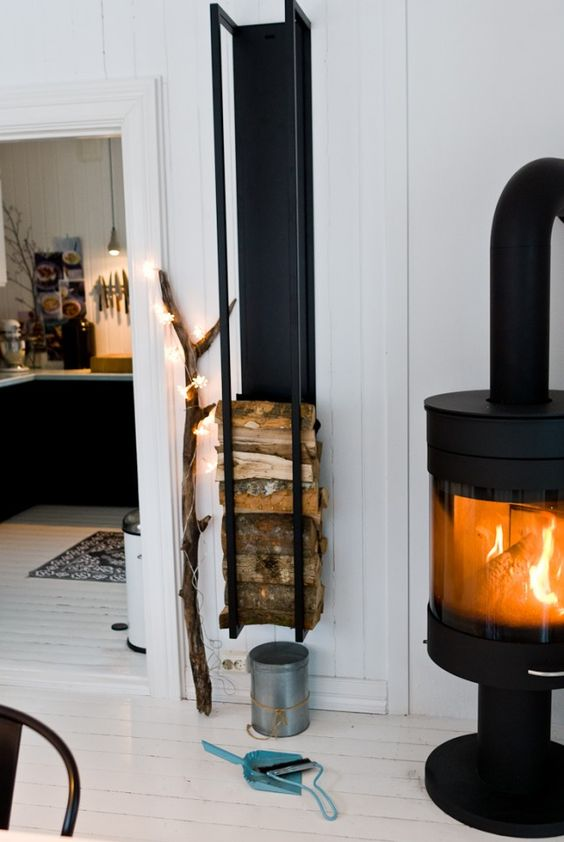 a modern wood stove and a wall-mounted firewood rack plus a branch with lights to make the space cooler