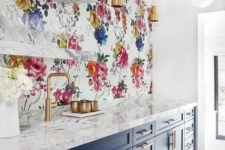 24 a navy kitchen with gold touches, white stone countertops and a colorful floral backsplash that makes a statement