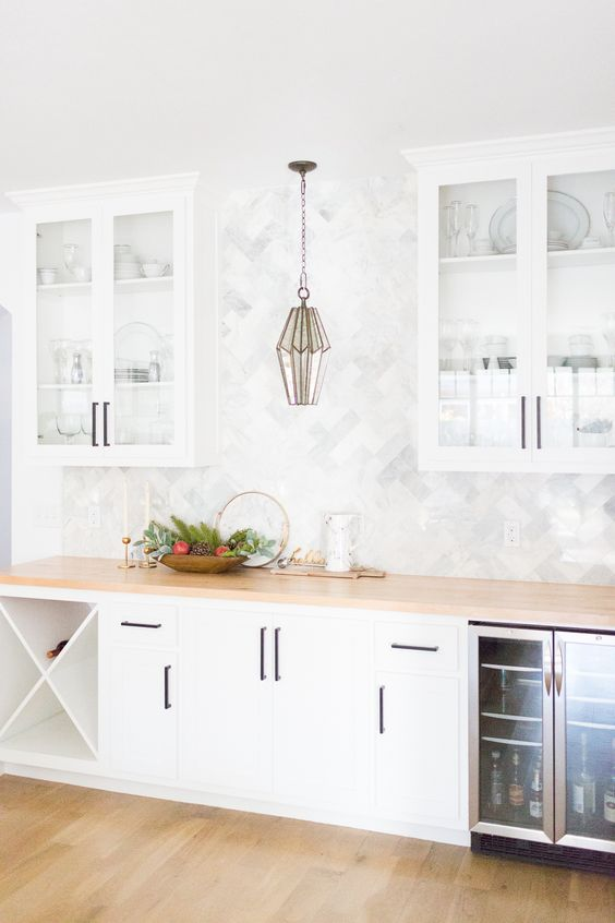 a neutral farmhouse kitchen with white cabinets, a wooden countertop and a marble tile backsplash plus a catchy pendant lamp