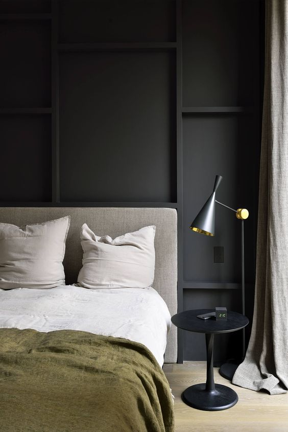 a stylish contemporary bedroom with a black paneled wall for an accent and some other black touches for more chic