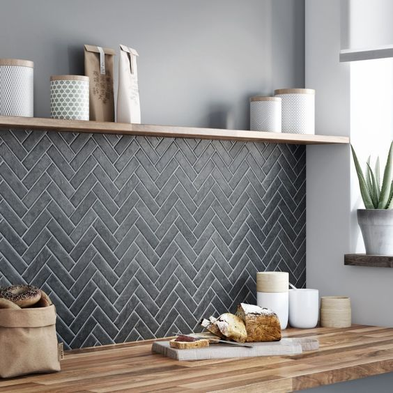 graphite grey tiles clad in a chevron pattern and look stylish with butcher block countertops
