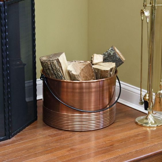 a copper bucket is a great and simple idea to store some firewood with a rustic feel