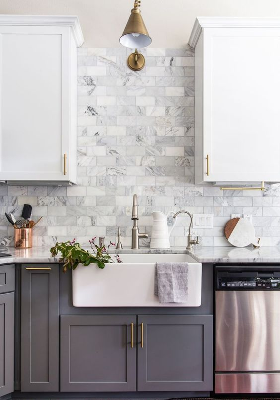 a stylish two-tone kitchen in grey and white, with brass abnd gold touches and a chic marble tile backsplash