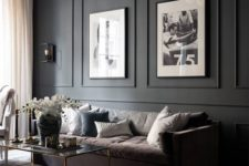 25 a super elegant living room with a black paneled wall and artworks that are fit into paneling looks very stylish