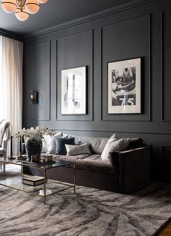a super elegant living room with a black paneled wall and artworks that are fit into paneling looks very stylish