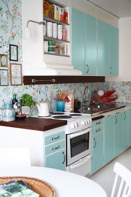 a turquoise kitchen and a matching blue wallpaper backsplash with a floral print for a cute and homey feel