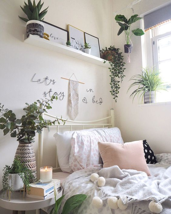 a neutral bedroom with potted greenery and plants, with candles and some minimalist artworks looks cool