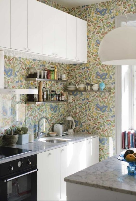 a neutral kitchen with grey stone countertops and a bright printed wallpaper backsplash covered with glass to protect it