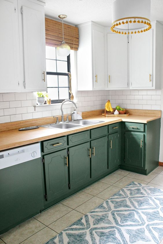 a stylish kitchen with white upper cabinets and hunter green lower ones, brass handles and butcher block countertops plus woven shades