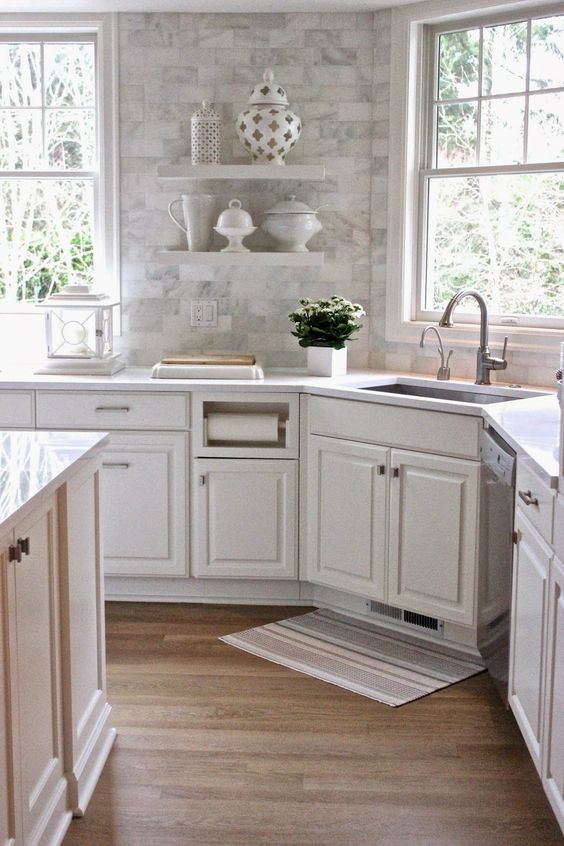 a white farmhouse kitchen with a marble tile backsplash, a white countertop and neutral fixtures for a cohesive feel