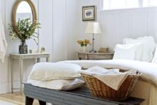 a French farmhouse bedroom in white, with vintage furniture of wood, elegant decor and some greenery