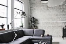 a Nordic meets industrial living room with a shabby wooden wall, a concrete table, metal lamps and some greenery in pots