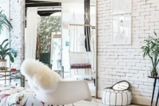 a Scandinavian closet done in white, with brick walls and white furniture is filled with light and air