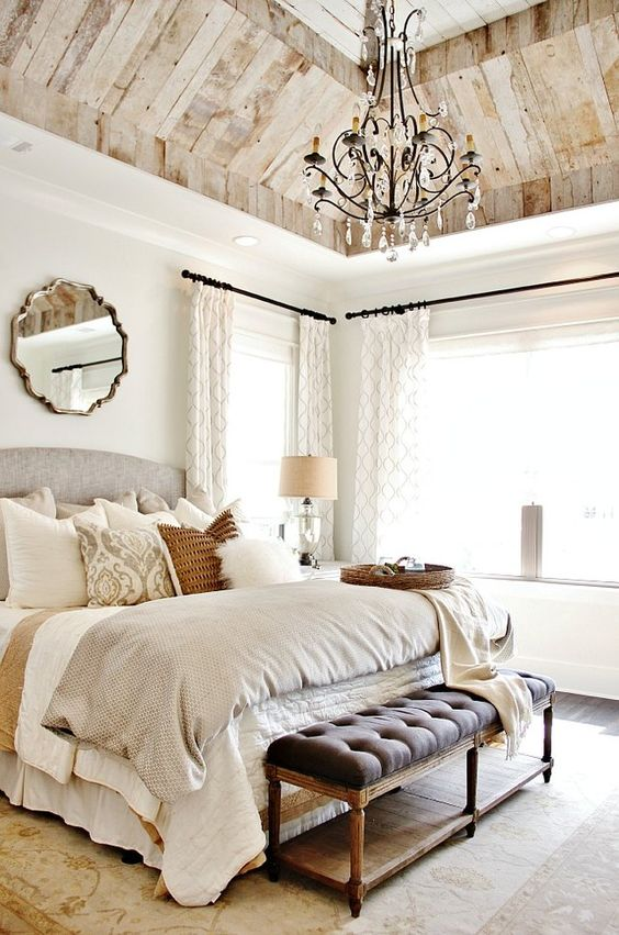 a beautiful farmhouse bedroom with a reclaimed wooden ceiling, a vintage chandelier, an upholstered bed and bech, catchy bedding and pillows