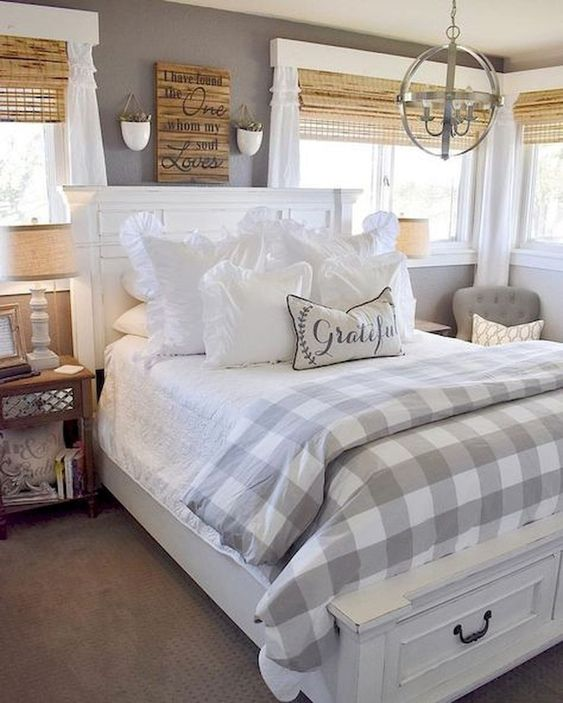 a beautiful farmhouse bedroom with grey walls, woven shades, white and natural wood furniture, a vintage chandelier and buffalo check