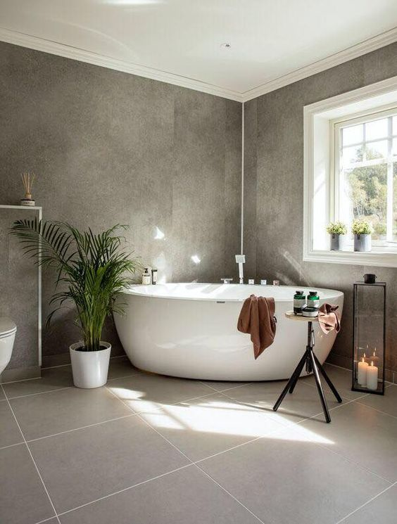 a beautiful grey bathroom with two kinds of tiles, potted plants, a free standing tub, a candle lantern and a table