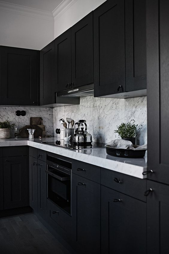 a black framhouse kitchen with white marble countertops and a backsplash is a chic and stylish idea