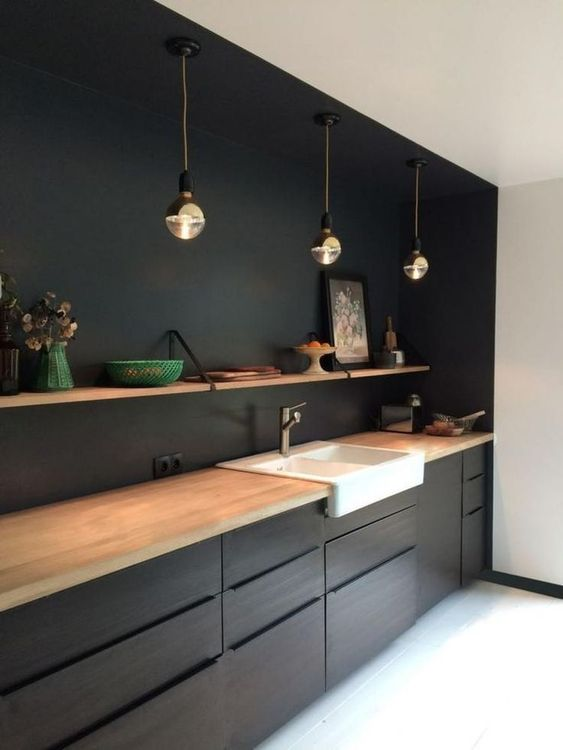 a black kitchen with light-colored wood countertops, pendant lamps and open shelving over the cabinets
