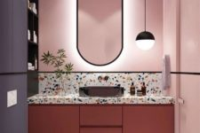a bold bathroom with pink walls, a coral vanity, a terrazzo countertop and bold graphic tiles on the floor