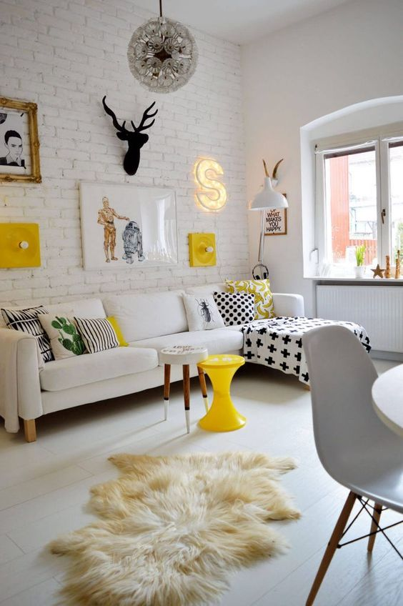 a bold contemporary living room with a white brick wall and a gallery wall with lots of signs, lights and artworks