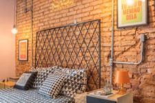 a bold industrial bedroom with red brick walls, exposed pipes, a metal bed, catchy nighstands with casters