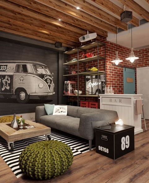 a bold industrial living room with red brick walls, a wooden ceiling, comfy furniture, a wooden table on casters and a crochet ottoman