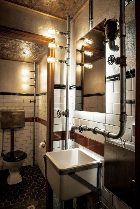 a bold industrial powder room with various tiles, exposed piping, metal fixtures and stands plus bulbs